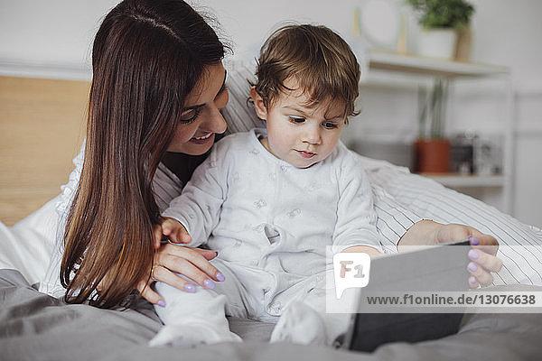 Glückliche Mutter mit Tablet-Computer und Baby-Boy im Bett