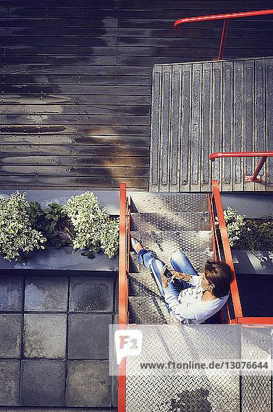 Draufsicht einer Frau  die ein Mobiltelefon benutzt  während sie auf Stufen vor einem Café sitzt