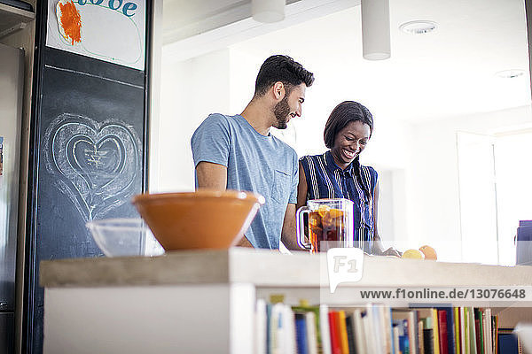 Happy couple preparing food at kitchen counter