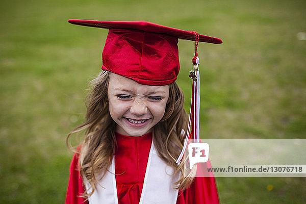 Happy girl in graduation gown on field