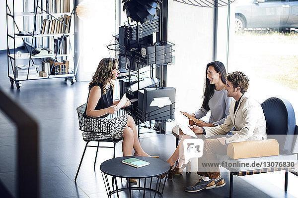 Hoher Blickwinkel auf glückliche Geschäftsleute  die im Büro auf dem Sofa sitzend diskutieren
