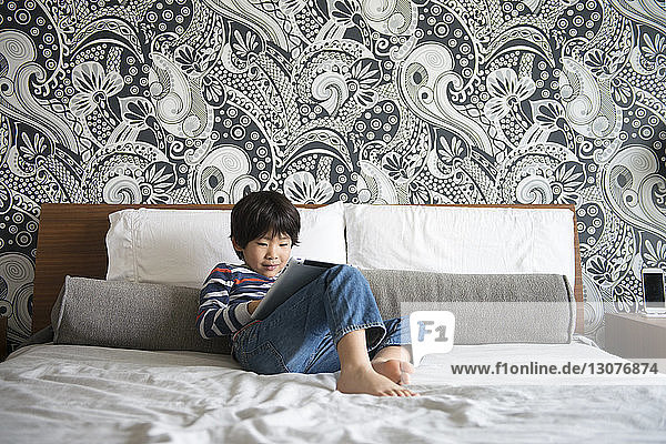 Boy sitting on bed and using digital tablet
