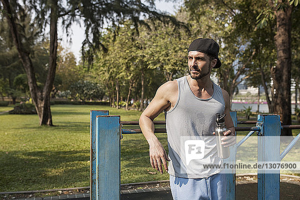 Man holding water bottle after exercising at park