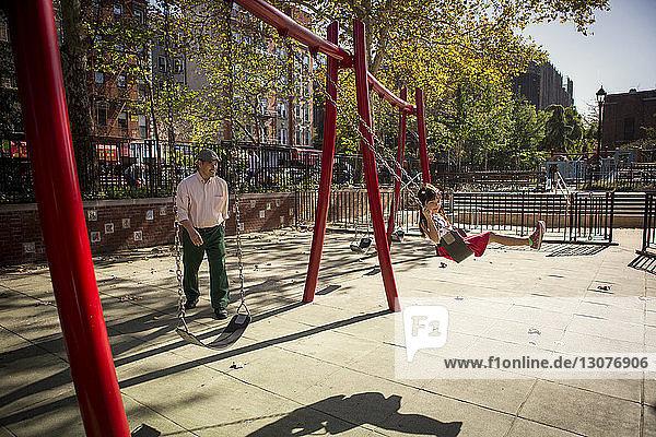 Großvater schaut auf Enkelin  die auf einer Schaukel im Park sitzt