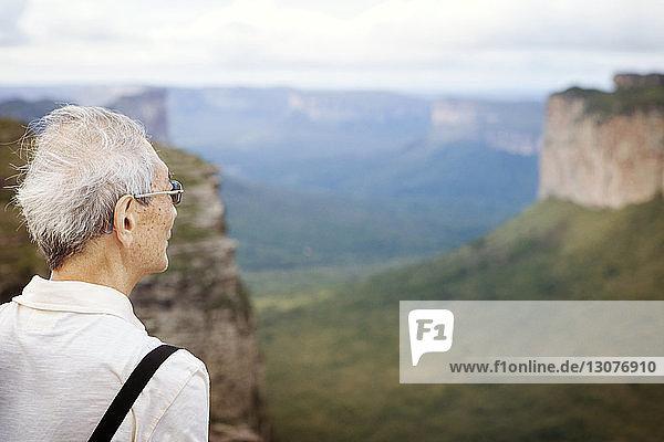 Älterer Mann schaut auf Klippen