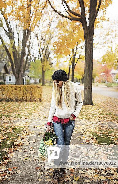 Frau hält Einkaufstasche und steht auf unordentlichem Fußweg