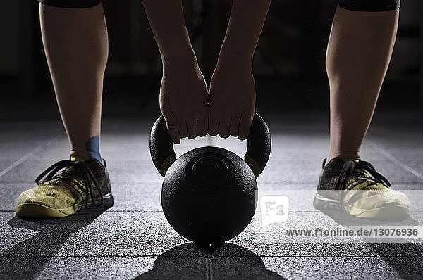 Low section of athlete lifting kettle bell at gym