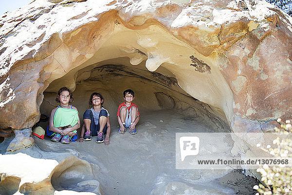 Vorderansicht der in der Höhle sitzenden Geschwister