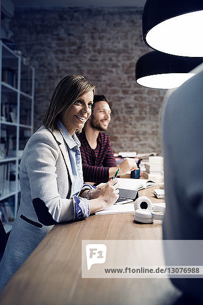 Happy businesswoman looking at colleague in conference room