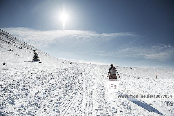 Rückansicht einer Frau  die an einem sonnigen Tag auf einem schneebedeckten Feld gegen den Himmel läuft