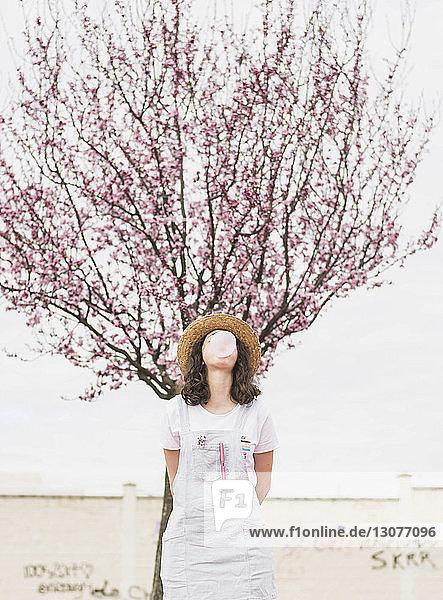 Verspielte junge Frau bläst Kaugummi  während sie im Park an einem Kirschbaum steht