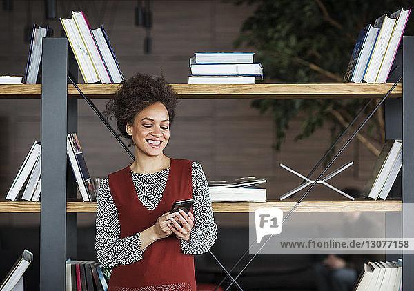 Glückliche Geschäftsfrau benutzt Smartphone  während sie gegen ein Bücherregal steht