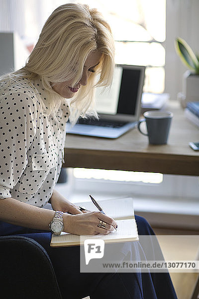 Side view of woman writing in diary while working at home