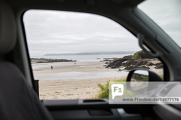 Scenic view of sea against cloudy sky seen through motor home window