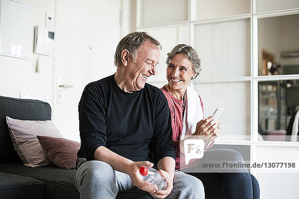 Happy senior couple using smart phone in living room