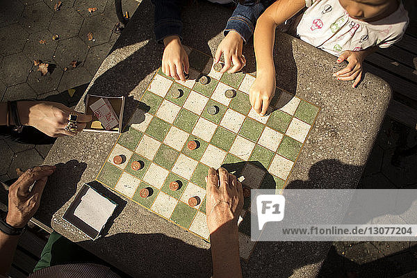 Overhead view of girls playing checkers game with grandfather at table in park