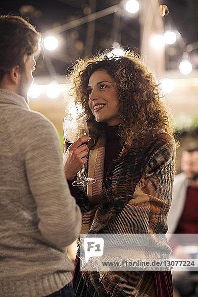 Frau mit Wein spricht nachts im Garten mit einem Freund