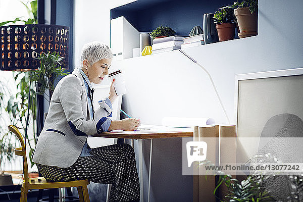 Female architect working while having coffee in office