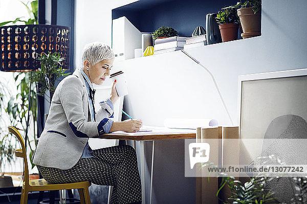 Architektin arbeitet  während sie im Büro Kaffee trinkt