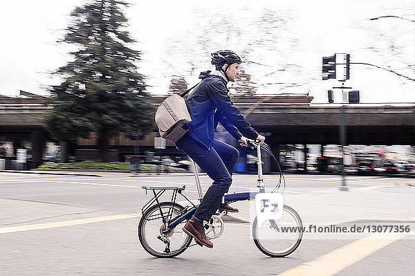 Side view of businessman riding bicycle on city street