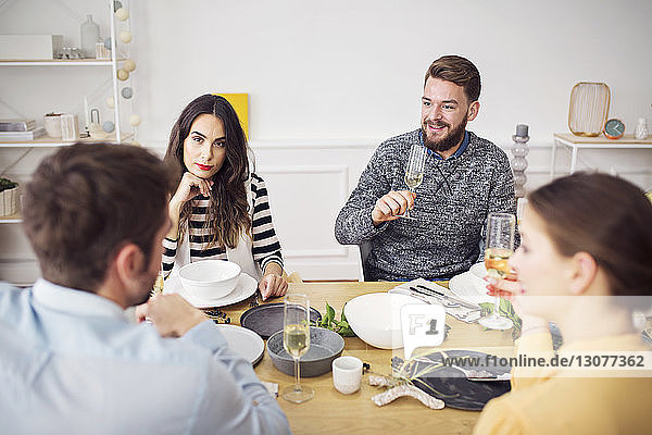 Friends discussing while sitting at table in lunch party