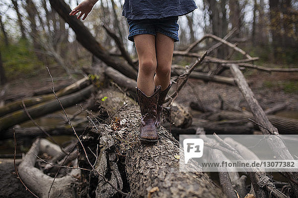 Low section of girl walking on tree trunk in forest