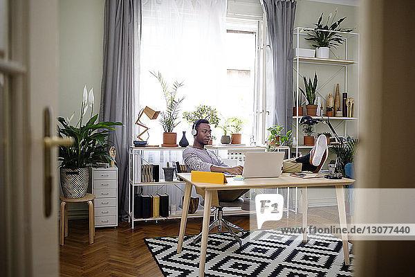 Entspannter Mann benutzt Laptop im Heimbüro