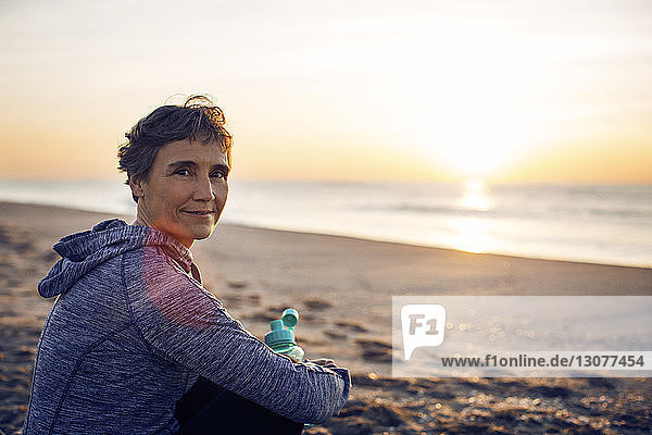 Portrait of smiling senior woman resting at beach