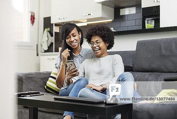 Glückliche Freunde genießen Musik über ein Smartphone  während sie auf dem Sofa sitzen