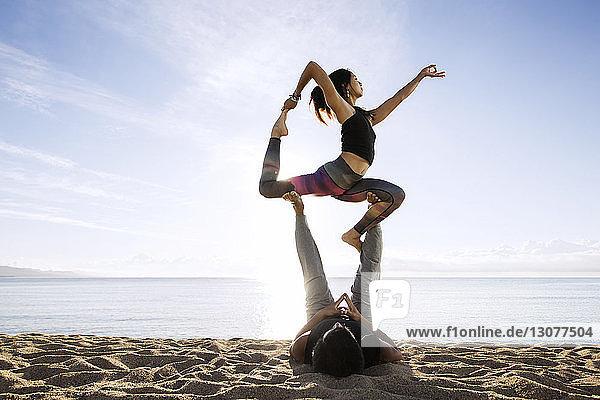 Ein Paar macht Yoga am Strand gegen den Himmel