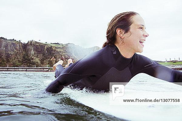 Happy woman lying on surfboard in sea against sky