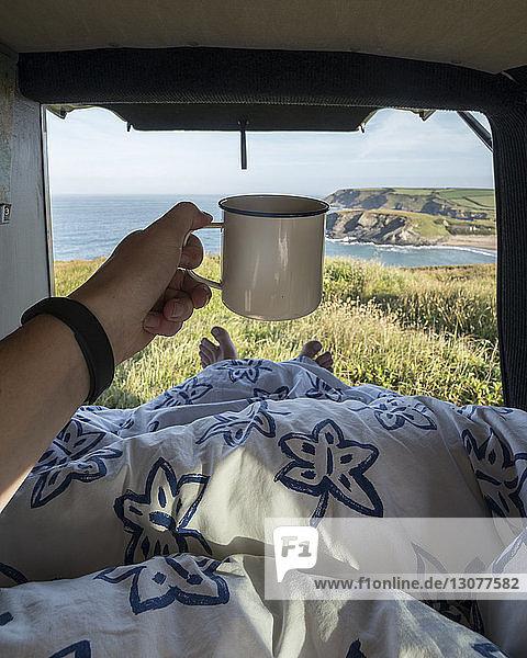 Niedriger Abschnitt eines Mannes  der eine Tasse hält  während er sich im Wohnmobil auf dem Bett entspannt