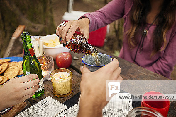 Cropped image of woman pouring beer for friend while sitting at picnic table in forest