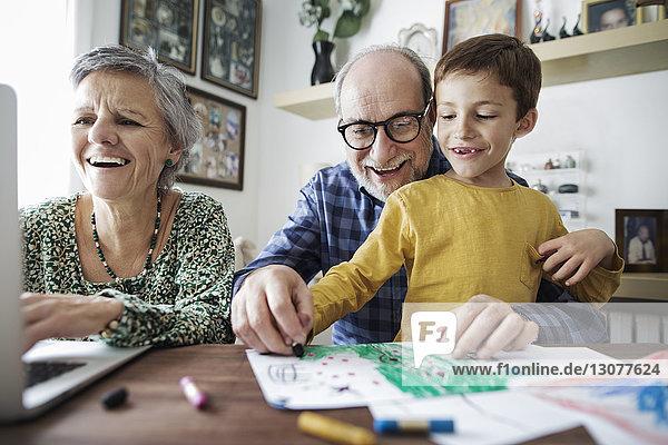 Fröhliche Großeltern mit Enkel beim Zeichnen zu Hause