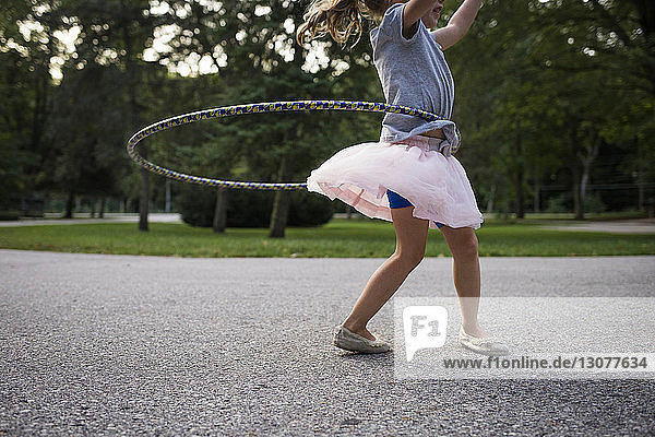 Low angle view of girl playing with hula hoop on footpath