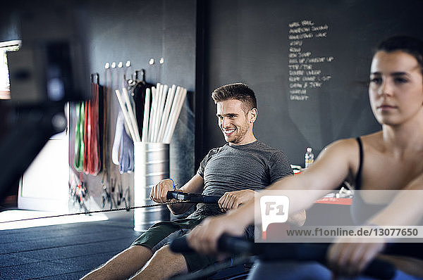 Happy man exercising on rowing machine in gym