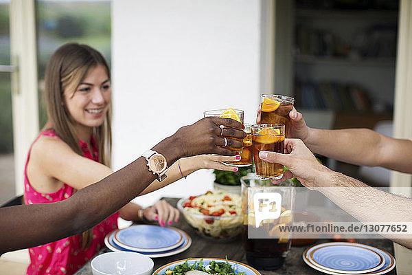 Frau trinkt Eisteegläser mit Freunden an einem Tisch im Freien