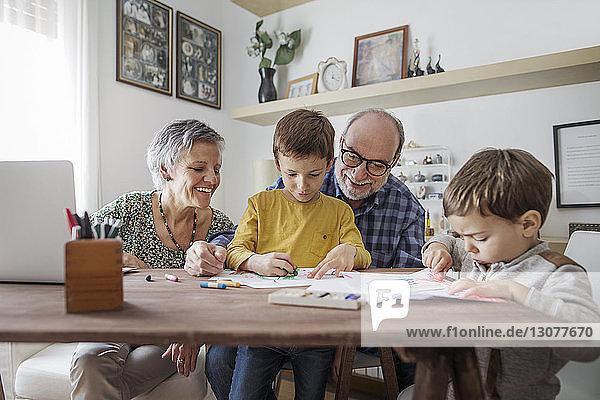 Happy grandparents looking at grandsons making drawings at home