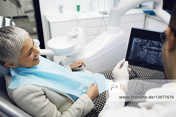 Dentist showing x-ray to happy woman at clinic