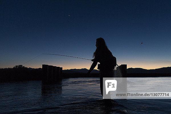Silhouette einer jungen Frau beim Fliegenfischen  die in der Dämmerung im Fluss Owens gegen den Himmel steht