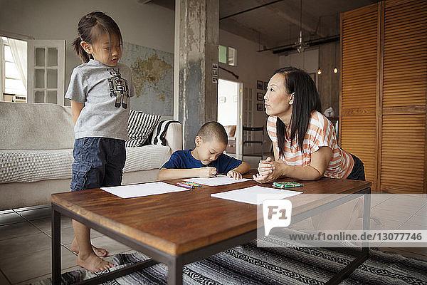 Mädchen im Gespräch mit der Mutter  während der Bruder am Tisch im Wohnzimmer zeichnet