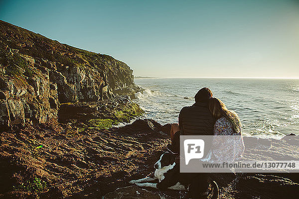 Couple and dog sitting on rock by sea against clear sky