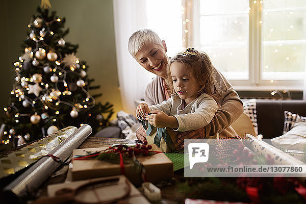Girl and grandmother packing gift at table during Christmas