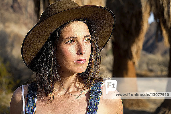 Thoughtful young woman wearing hat while looking away at desert