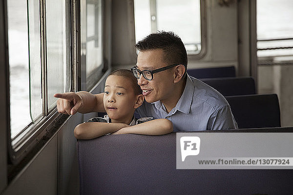 Father showing son while enjoying in ferry