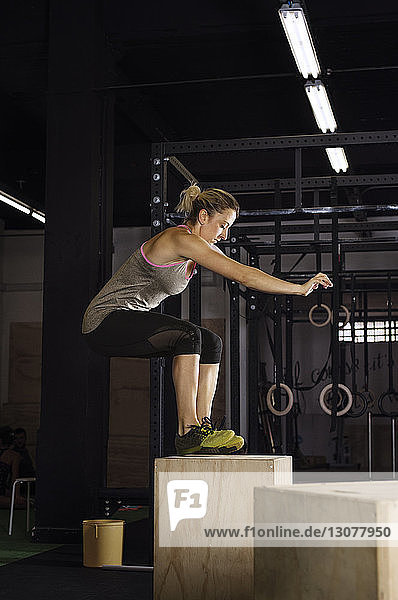 Side view of confident female athlete doing box jumping at gym