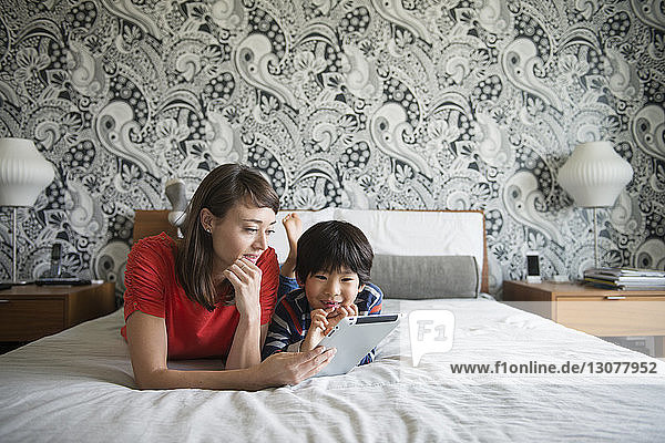 Mother and son using digital tablet while lying on bed