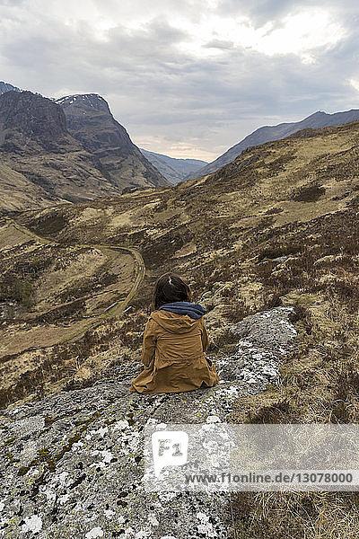 Rückansicht einer auf einem Berg sitzenden Frau vor bewölktem Himmel