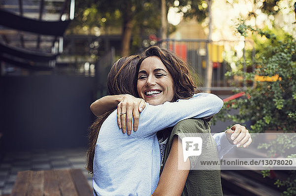 Liebevolle reife Frauen umarmen sich im Straßencafé