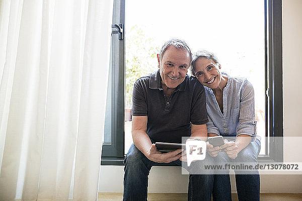 Porträt eines glücklichen älteren Ehepaares mit Smartphone und Tablet-Computer in der Hand  während es zu Hause auf dem Fensterbrett sitzt